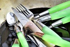 Las cucharas, las bifurcaciones y los cuchillos sucios están en la cacerola vieja en el fregadero af foto de archivo libre de regalías