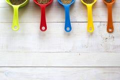 Las cucharas dosificadoras coloridas con las especias para la cocina en un blanco cortejan Imagen de archivo libre de regalías