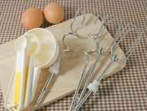 Las cucharas dosificadoras plásticas con el metal baten y Egg Fotos de archivo libres de regalías