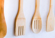 Las cucharas y las bifurcaciones de madera cuelgan en la pared imagen de archivo