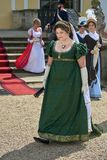 Las damas y caballeros en trajes históricos de la época de Napoleon Bonaparte tienen un paseo en parque foto de archivo libre de regalías
