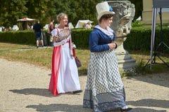 Las damas y caballeros en trajes históricos de la época de Napoleon Bonaparte tienen un paseo en parque fotos de archivo