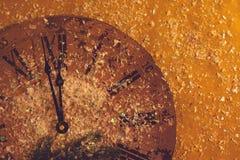 Las decoraciones chispeantes de la tarjeta de la celebración del fondo de la Feliz Año Nuevo miran el vintage del reloj broncear imagen de archivo libre de regalías