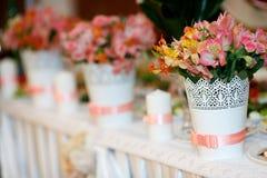 Las decoraciones de la flor con las cintas rosadas se colocan en la tabla de la boda Imágenes de archivo libres de regalías