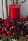 Las decoraciones de la Navidad con las velas rojas y el pino ramifican en el interior blanco Imágenes de archivo libres de regalías