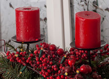 Las decoraciones de la Navidad con las velas rojas y el pino ramifican en el interior blanco Fotos de archivo libres de regalías