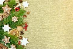 Las decoraciones de la Navidad del pan de jengibre con el abeto ramifican en el oro Imagen de archivo libre de regalías