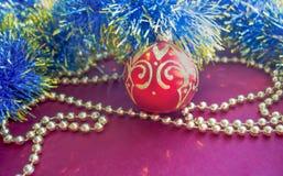 Las decoraciones de la Navidad, las gotas de oro, la malla azul y la bola roja con oro modelan, mienten en un fondo rojo Imagen de archivo libre de regalías