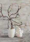 Las decoraciones de la Navidad se dirigen el interior - ramas secas en un florero blanco y Santa Claus de cerámica en una tabla d Foto de archivo libre de regalías