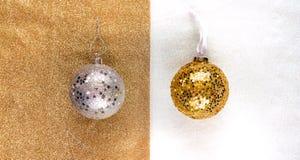 Las decoraciones del Año Nuevo de oro y las bolas de plata con las estrellas brillan en un fondo de oro y blanco, dividido por la Fotografía de archivo