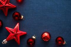 Las decoraciones rojas de la Navidad protagonizan y las bolas en fondo azul marino de la lona Tarjeta de la Feliz Navidad Fotos de archivo libres de regalías