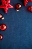 Las decoraciones rojas de la Navidad protagonizan y las bolas en fondo azul marino de la lona Tarjeta de la Feliz Navidad Fotografía de archivo