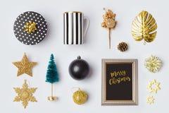 Las decoraciones y los objetos en negro y el oro de la Navidad para la mofa encima de la plantilla diseñan Visión desde arriba foto de archivo