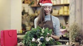 Las demostraciones de la muchacha en un delantal y del sombrero de la Navidad enrruellan, cámara van de parte inferior al top almacen de metraje de vídeo
