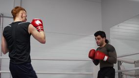 Las demostraciones del instructor de Kickboxing y explicar técnica del soplo de la pierna del deportista golpean con el pie en el metrajes