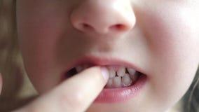 Las demostraciones del niño de la muchacha primero ordeñan el diente temporal metrajes