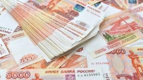 Las denominaciones de cinco mil rublos dispersaron en la tabla, un fondo con pantalla grande Fotos de archivo
