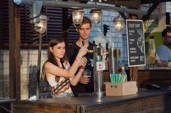Las dependientas jovenes vierten la cerveza fría del barrilete en el contador del festival de la comida de la calle Fotografía de archivo