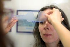 Las dimensiones experimentadas bonitas del tamaño del alumno del ojo de la mujer joven prueban con el óptico del optometrista del fotografía de archivo libre de regalías