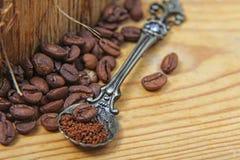 Las diversas clases del primer de granos de café dispersaron en un fondo de madera, cuchara del café molido en el espacio vacío d Foto de archivo