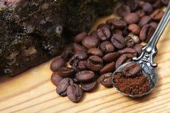Las diversas clases del primer de granos de café dispersaron en un fondo de madera, cuchara del café molido en el espacio vacío d Fotos de archivo