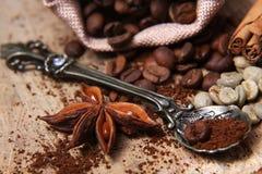 Las diversas clases del primer de granos de café, café verde, estrella del anís, dispersaron en un fondo de madera, cuchara del c Foto de archivo