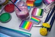 Las diversas herramientas y pinturas para el maquillaje de la aguamarina y el arte de cuerpo están en la tabla Imágenes de archivo libres de regalías