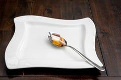 Las diversas píldoras están en una cuchara al lado de una placa blanca en una tabla marrón imagenes de archivo