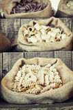 Las diversas pastas en lona empaquetan en el tablero retro de madera Fotografía de archivo libre de regalías