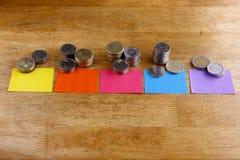 Las diversas pilas o pilas de monedas con el papel coloreado marcan con etiqueta Fotografía de archivo