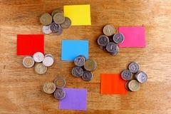 Las diversas pilas o pilas de monedas con el papel coloreado marcan con etiqueta Imagen de archivo libre de regalías
