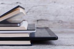 Las diversas tabletas están entre una pila de libros En un fondo de madera Primer fotos de archivo libres de regalías
