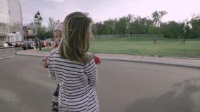 Las dos hermanas hermosas jovenes felices están montando un hydroskater en el camino en el parque almacen de metraje de vídeo