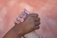Las dos manos de los childrende differents compiten con juntas Foto de archivo libre de regalías