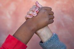 Las dos manos de los childrende differents compiten con juntas Foto de archivo