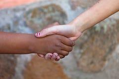 Las dos manos de los childrende differents compiten con juntas Imágenes de archivo libres de regalías