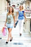 Las dos mujeres van a hacer compras en una alameda Foto de archivo libre de regalías