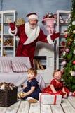 Las dos niñas con Papá Noel en el estudio con las decoraciones de la Navidad Fotografía de archivo libre de regalías
