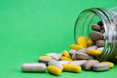Las drogas de las vitaminas dispersaron y se derramaron hacia fuera cerca de un envase de cristal blanco abierto del tarro Tratam fotos de archivo libres de regalías
