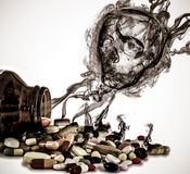 Las drogas que vierten de la botella con peligro del cráneo firman la flotación hacia fuera foto de archivo libre de regalías