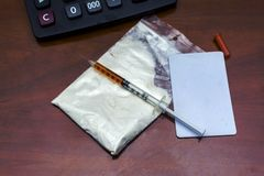Las drogas se pulverizan y una jeringuilla en oficina del escritorio Imagen de archivo