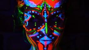 Las emociones del primer de jóvenes bodyarted a la muchacha del avatar en la luz ultravioleta Cara de la mujer en luz del color almacen de video