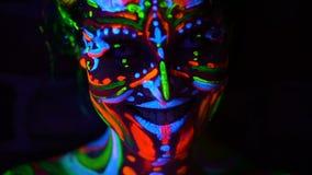 Las emociones del primer de jóvenes bodyarted a la muchacha del avatar en la luz ultravioleta Cara de la mujer en luz del color metrajes