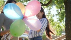 Las emociones en día soleado, hembra alegre con los globos coloridos felicitan feliz cumpleaños del amigo en parque almacen de metraje de vídeo