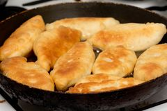 Las empanadas se fríen en una cacerola Foto de archivo