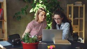 Las empresarias están trabajando en el proyecto juntas usando el ordenador portátil, después están haciendo el alto cinco para ce almacen de metraje de vídeo