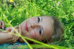 Las endechas de la chica joven en una hierba fotografía de archivo libre de regalías