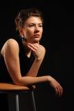 Las endechas hermosas del brunette en una silla Imagenes de archivo