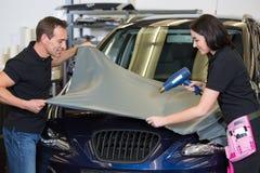 Las envolturas del coche atan la hoja gris del vinilo al vehículo Imagen de archivo libre de regalías