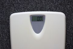 Las escalas electrónicas blancas con número ponen a cero el kilogramo en fondo gris de la alfombra Imagen de archivo libre de regalías